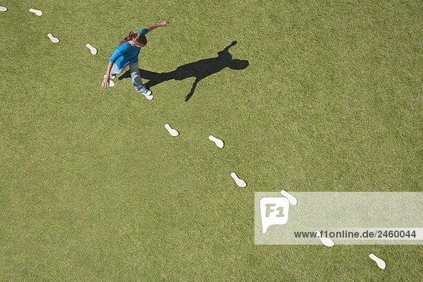 Junges Mädchen nach Fußabdrücke auf Gras