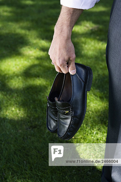 Kaufmann seine Schuhe in seine Hand Stockholm Schweden hält.
