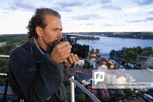 Ein Mann mit einer Kamera mit einem Blick über Stockholm Schweden.