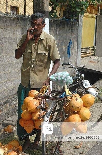 Galle Sri Lanka: ein Kokosnüsse Verkäufer Rauchen in der Straße