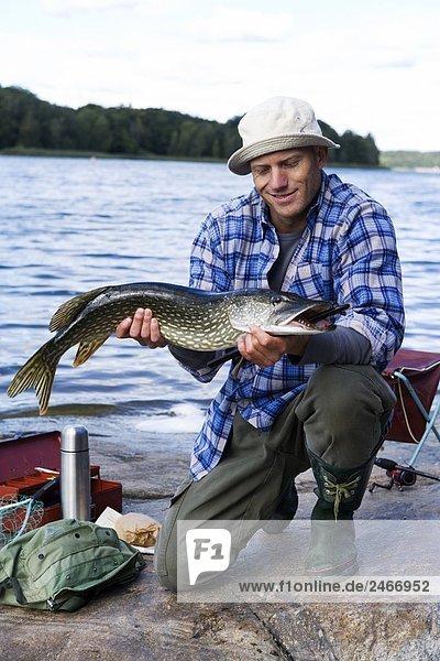Ein Mann  der eine Pike Schweden hält.