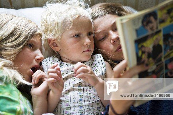 Drei Schwestern lesen eine Comic Papier zusammen Schweden.