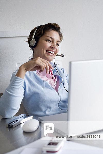 Frau mit Kopfhörer und laptop