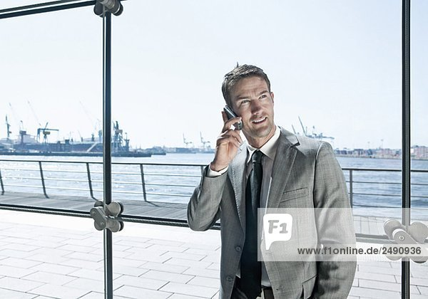 Man using a mobile phone in a glassbuilding