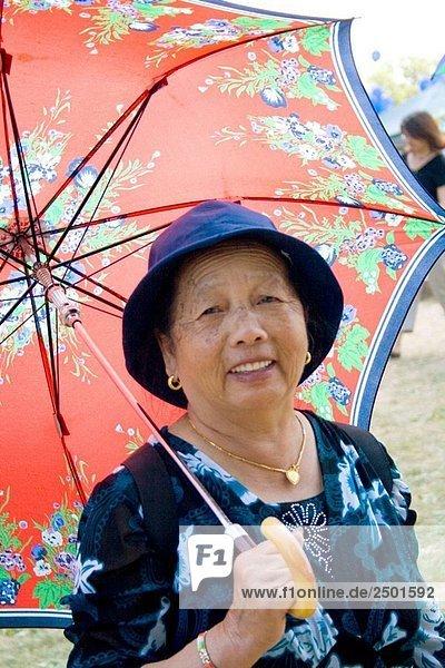 Hmong Frau genießen einen Spaziergang mit ihren bunten Sonnenschirm Hmong Sports Festival McMurray Feld St. Paul Minnesota USA