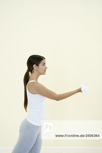 Junge Frau beim Heben von Gewichten  Seitenansicht