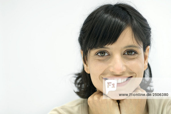 Frau lächelt vor der Kamera  Hände unter dem Kinn  Porträt