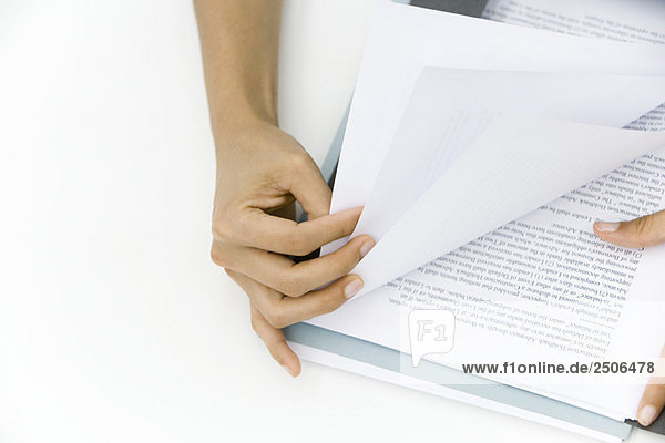 Person thumbing through pages of document  cropped view of hands