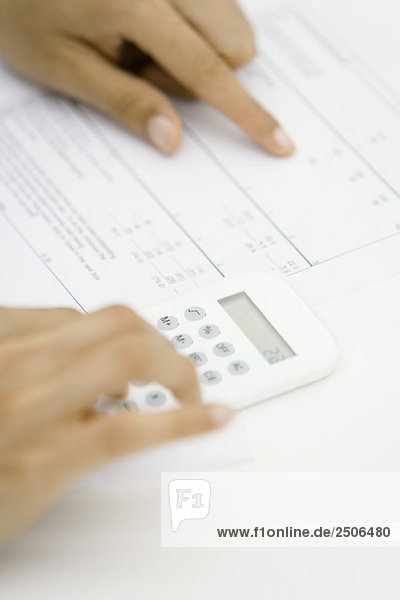 Person using calculator and pointing at document  cropped view of hands