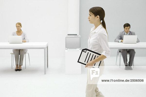 Büroangestellte mit Dokument unterm Arm  Kolleginnen im Hintergrund