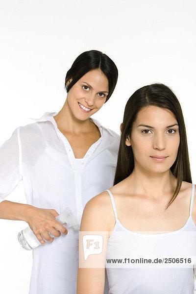 Junge Frau und Friseurin lächelnd vor der Kamera  Stylistin mit Sprühflasche