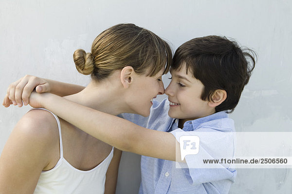 Mother and son touching noses  boy's arms around woman  side view