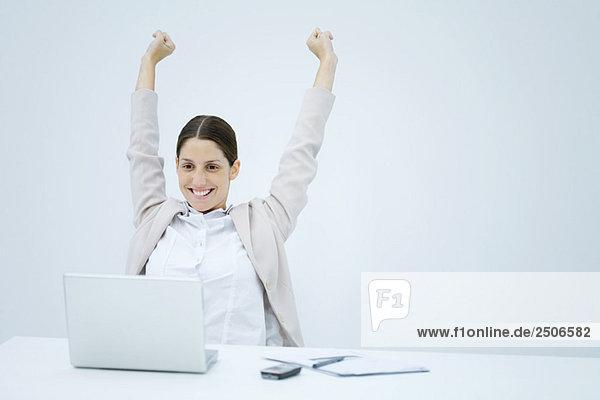 Junge Geschäftsfrau sitzt am Schreibtisch  lächelt den Laptop an und hebt beide Arme in die Luft.