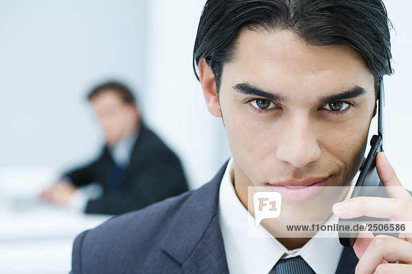 Young professional man holding cell phone  smirking at camera  portrait