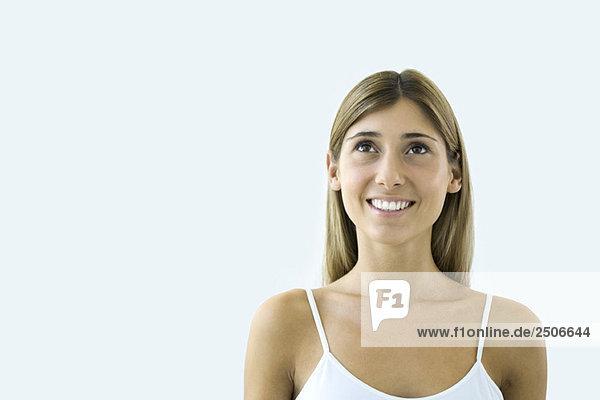Junge Frau schaut auf und lächelt  Porträt