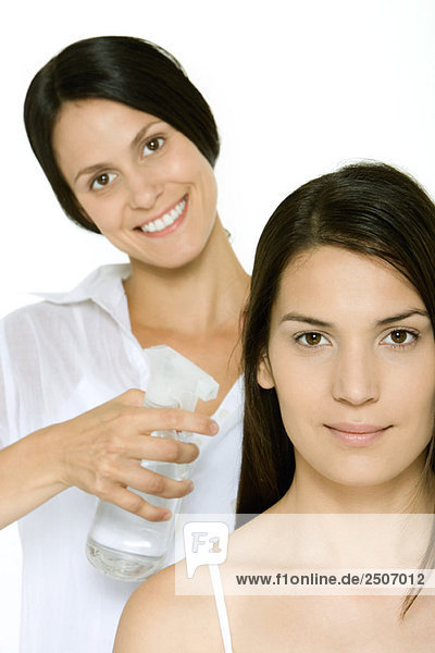Hair stylist spraying woman's hair  both smiling at camera