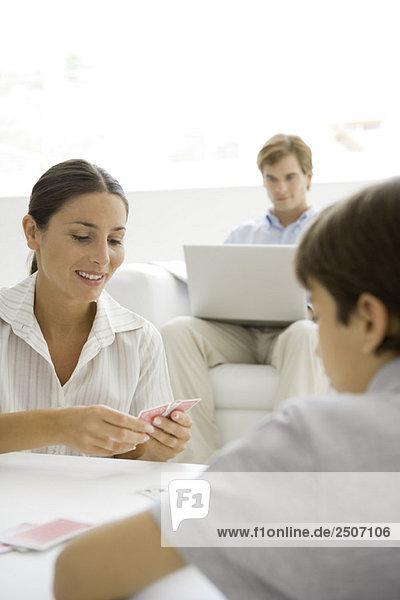 Frau spielt ein Kartenspiel mit ihrem Sohn  Ehemann sitzt im Hintergrund mit Laptop