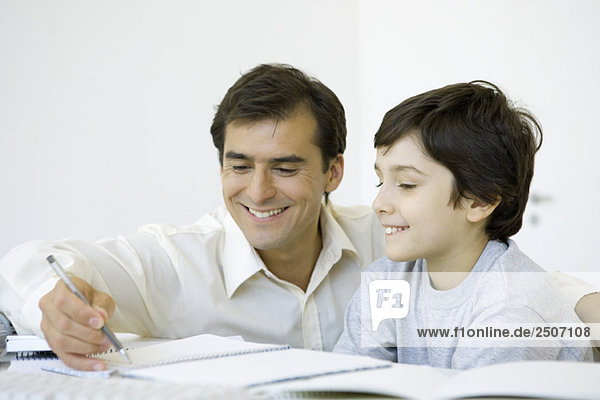 Father helping his son do homework  both smiling
