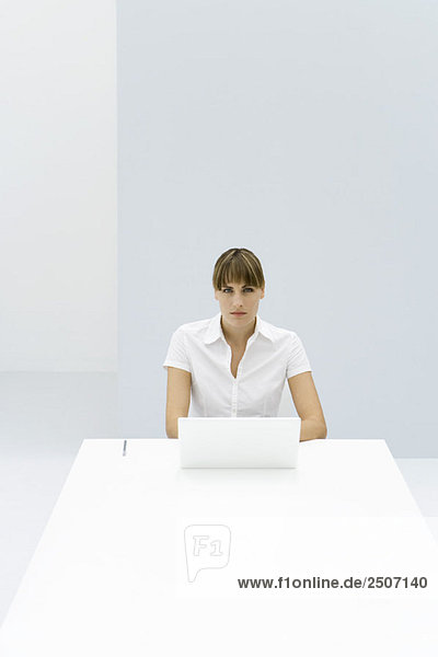 Woman sitting at table with laptop  looking at camera