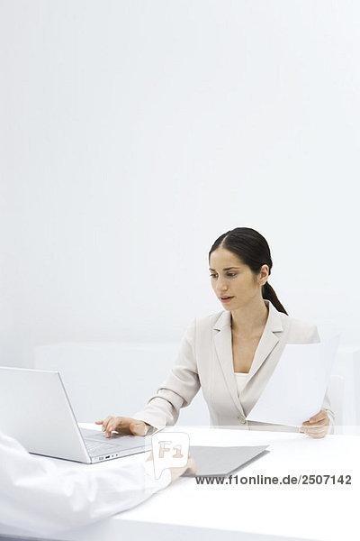 Frau  die einen Laptop benutzt  während sie ein Dokument hält  beschnittene Ansicht des Arms  der den Ordner über den Schreibtisch schiebt.
