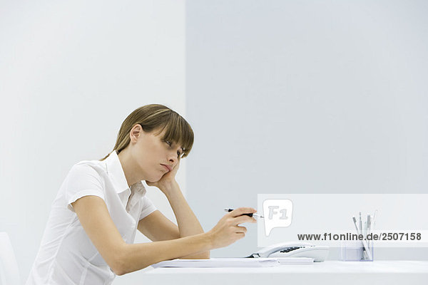 Woman sitting at desk  resting head in her hand  looking away and frowning