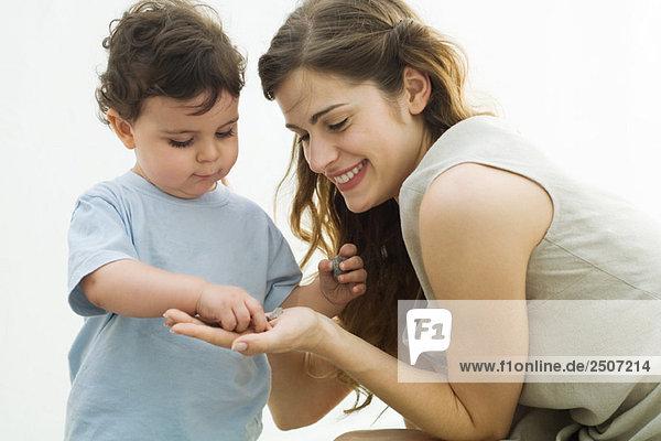 Junge Mutter mit Kieselsteinen für neugierige Kleinkinder