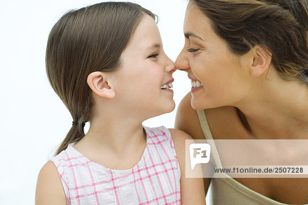 Mother and daughter touching noses,  smiling at each other,  close-up