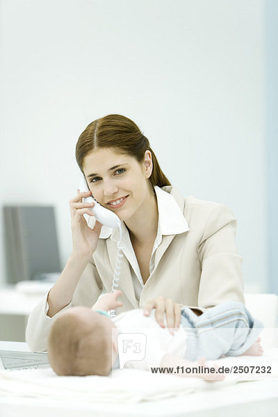 Professional woman using phone in office  smiling at camera  baby lying on desk
