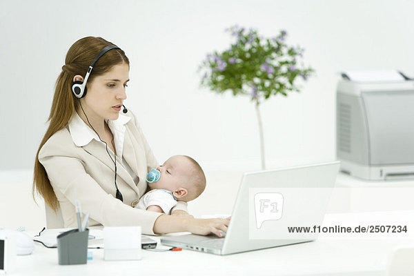 Businesswoman in office  holding sleeping baby  using headset and laptop computer