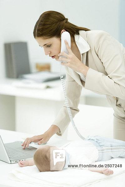 Professionelle Frau mit Telefon und Laptop  Baby liegt auf dem Schreibtisch neben ihr.