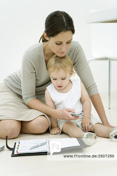 Professionelle Frau auf dem Boden sitzend mit Kleinkind und Agenda  wählend Handy