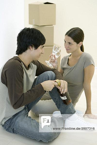 Paar auf dem Boden sitzend  Frau hält Weingläser  Mann öffnet Weinflasche