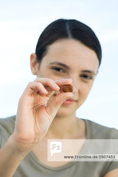 junge Frau hält Puffbohnen zwischen den Fingern  zeigt es an Kamera
