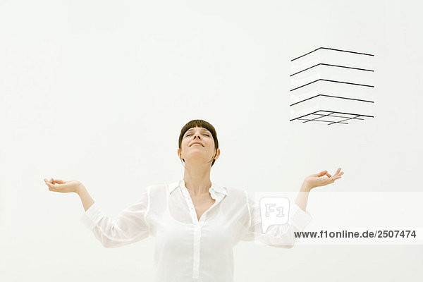 Woman meditating  cube hovering in midair over her left hand  head back  eyes closed