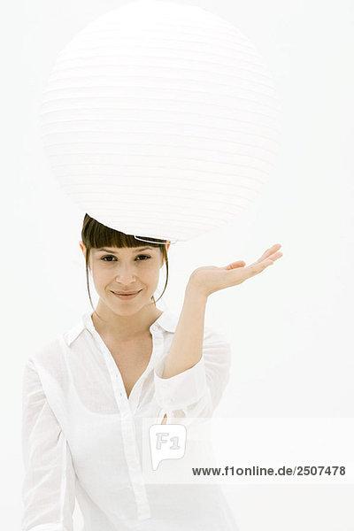 Frau suchen unter Papierlaterne  Lächeln in die Kamera Frau suchen unter Papierlaterne, Lächeln in die Kamera