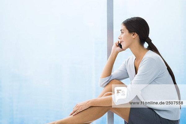 Frau sitzt mit Beinen  bis auf Handy  sprechen aus Fenster Suchen