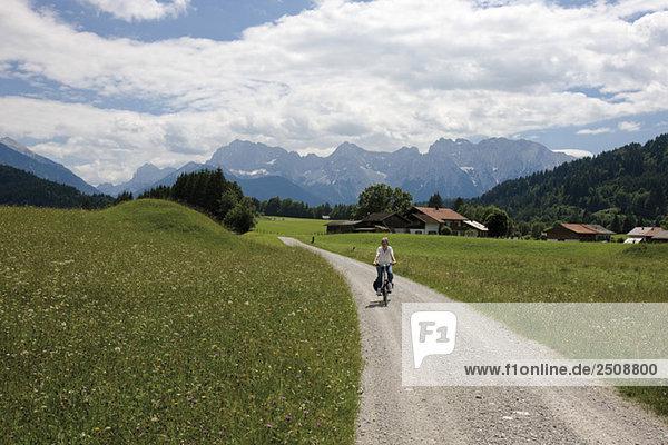 Werdenfelser Land  Junge Frau beim Radfahren auf der Landstraße