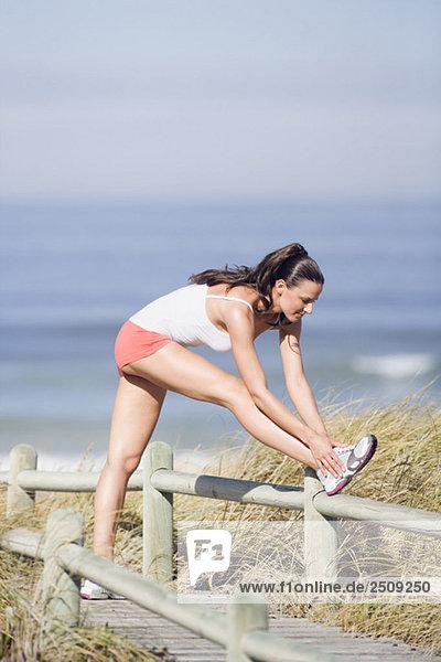 Junge Frau streckt Bein,  Seitenansicht