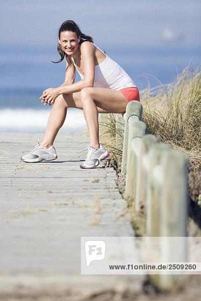 Junge Frau lächelnd  auf dem Zaun sitzend