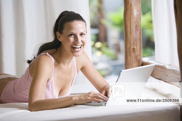 Junge Frau in Unterwäsche mit Laptop