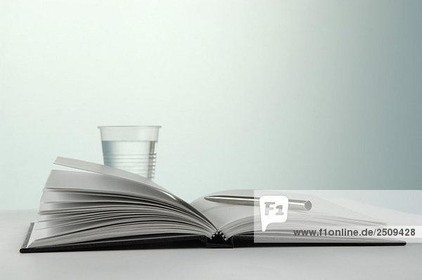 Wasserglas mit Stift und Notizbuch