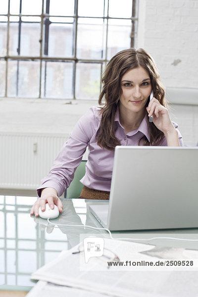 Junge Geschäftsfrau bei der Arbeit am Laptop  mit dem Handy