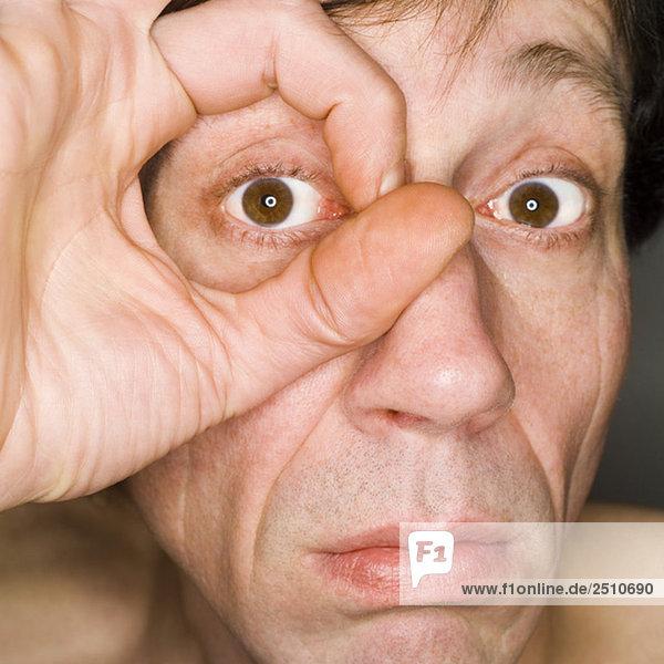 Männergesicht  Finger umrahmen das Auge  Nahaufnahme