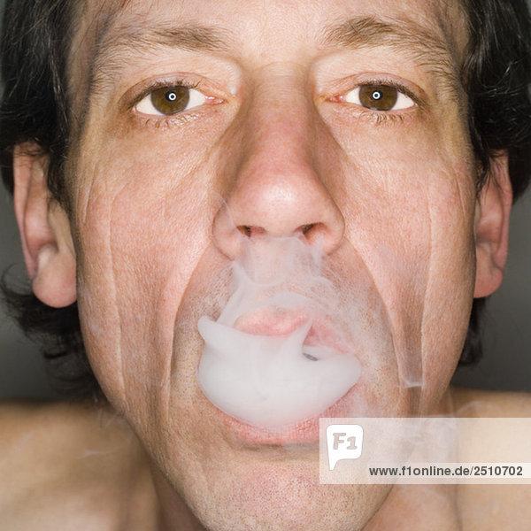 Mann beim Ausatmen von Zigarettenrauch  Nahaufnahme  Portrait