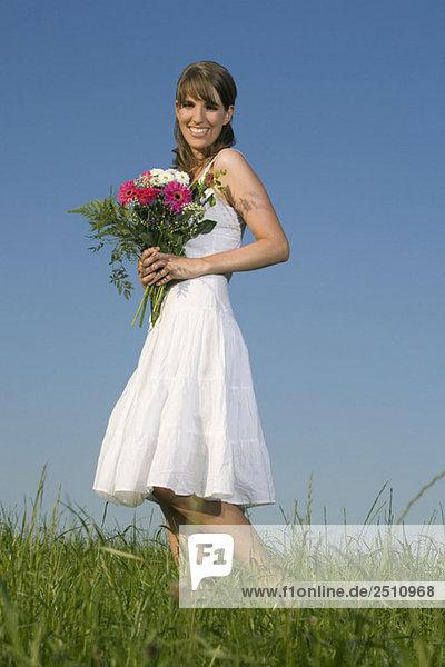 Junge Frau auf der Wiese  Blumenstrauß haltend  lächelnd  Portrait