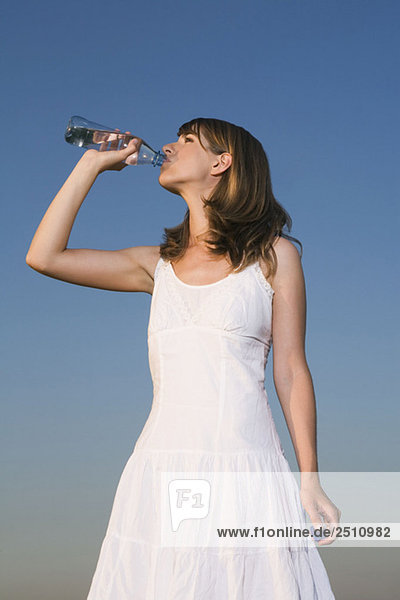 Junge Frau trinkt Wasser aus der Flasche  Porträt