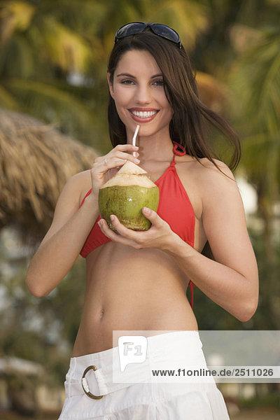 Asien  Thailand  Junge Frau mit Kokosnusscocktail  lächelnd  Portrait