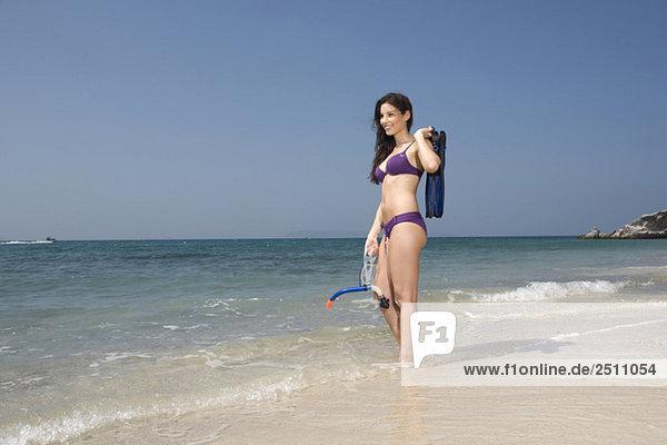 Asien  Thailand  Junge Frau am Strand  mit Flossen und Taucherbrille