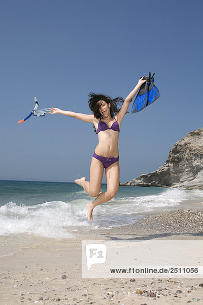 Asia  Thailand  Young woman jumping on beach