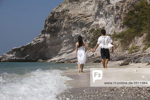 Asien  Thailand  Junges Paar geht Hand in Hand am Strand entlang  Rückansicht
